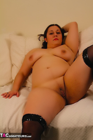 Cute BBW reveals her large breasts in red and black dress and black stockings then gets naked and expose her indulging twat as she opens her legs wide on a white couch. - XXXonXXX - Pic 19