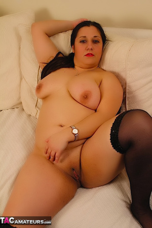 Cute BBW reveals her large breasts in red and black dress and black stockings then gets naked and expose her indulging twat as she opens her legs wide on a white couch. - XXXonXXX - Pic 20