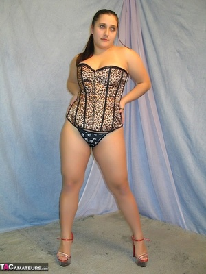 Hot BBW peels down her black and white thong and reveals her juicy pussy then takes off her black, brown and white corset and expose her large breasts in different poses wearing her red and clear high heels in a blue studio. - XXXonXXX - Pic 13