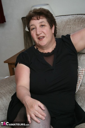BBW granny peels off her black dress and displays her large body in red nighty, black skirt, stockings and high heels on a gray and brown couch. - XXXonXXX - Pic 1