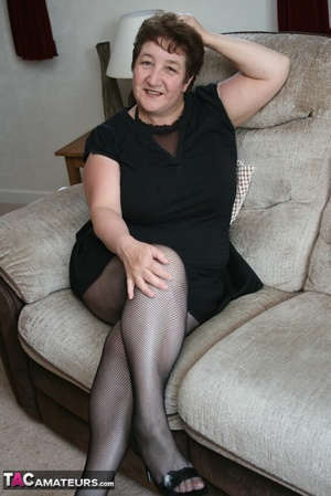 BBW granny peels off her black dress and displays her large body in red nighty, black skirt, stockings and high heels on a gray and brown couch. - XXXonXXX - Pic 2