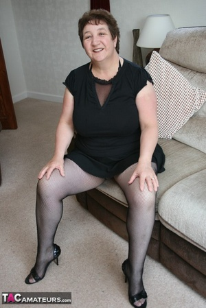 BBW granny peels off her black dress and displays her large body in red nighty, black skirt, stockings and high heels on a gray and brown couch. - XXXonXXX - Pic 5
