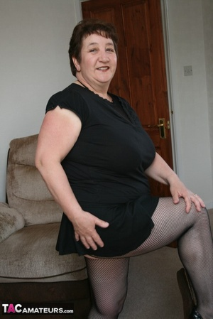BBW granny peels off her black dress and displays her large body in red nighty, black skirt, stockings and high heels on a gray and brown couch. - XXXonXXX - Pic 8