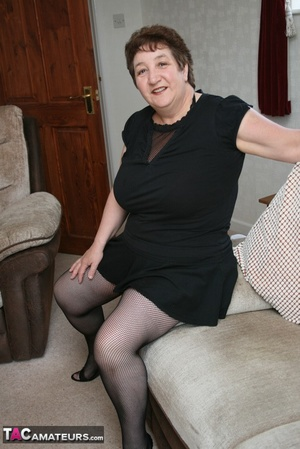 BBW granny peels off her black dress and displays her large body in red nighty, black skirt, stockings and high heels on a gray and brown couch. - XXXonXXX - Pic 9
