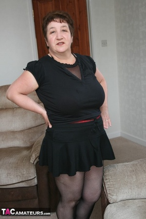 BBW granny peels off her black dress and displays her large body in red nighty, black skirt, stockings and high heels on a gray and brown couch. - XXXonXXX - Pic 10