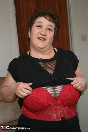 BBW granny peels off her black dress and displays her large body in red nighty, black skirt, stockings and high heels on a gray and brown couch. - XXXonXXX - Pic 11