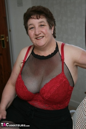 BBW granny peels off her black dress and displays her large body in red nighty, black skirt, stockings and high heels on a gray and brown couch. - XXXonXXX - Pic 12