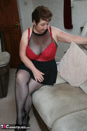 BBW granny peels off her black dress and displays her large body in red nighty, black skirt, stockings and high heels on a gray and brown couch. - XXXonXXX - Pic 13
