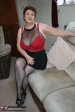 BBW granny peels off her black dress and displays her large body in red nighty, black skirt, stockings and high heels on a gray and brown couch. - XXXonXXX - Pic 14