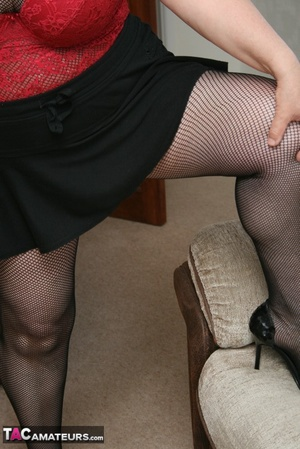 BBW granny peels off her black dress and displays her large body in red nighty, black skirt, stockings and high heels on a gray and brown couch. - XXXonXXX - Pic 16