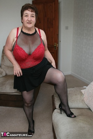 BBW granny peels off her black dress and displays her large body in red nighty, black skirt, stockings and high heels on a gray and brown couch. - XXXonXXX - Pic 18