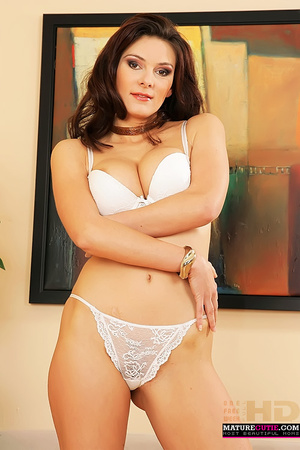 Big tits brunette sheds her lacy short dress and seductively posing in white underwear by the couch - XXXonXXX - Pic 7