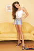 Long haired brunette seductively posing in jeans miniskirt and white top