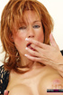 Mature redhead in black outfit fingering her pink pussy before dildoing