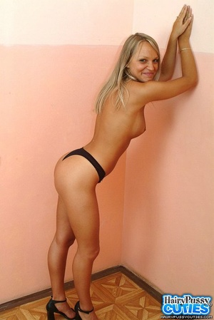 Busty blonde in black pants and undies stripteasing by the wall and showing her hairy coochie - XXXonXXX - Pic 7