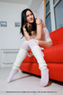 Black haired teen in white stockings sheds white bodysuit on the red couch