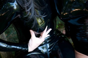 Brown eyed raven and blue eyed youngster wearing shiny latex suit outdoors on a bench - XXXonXXX - Pic 6