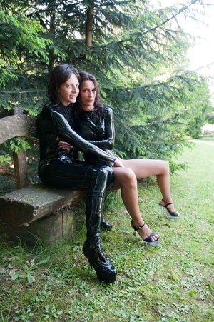 Brown eyed raven and blue eyed youngster wearing shiny latex suit outdoors on a bench - XXXonXXX - Pic 13
