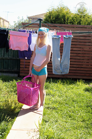 Luscious blonde peels off her white shirt then displays her skinny body in blue lingerie and bandana while she hangs and dry her clothes before she pulls down her bra and shows her tiny tits then strips down her panty and nails her twat with a purple dildo on the grass in her backyard. - XXXonXXX - Pic 3