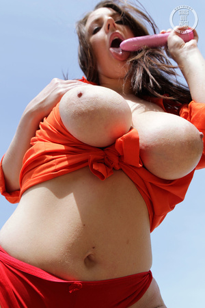 Alluring babe shows her huge tits as she displays her banging body before she strips off her blue and white shorts and nails her twat with a pink dildo in different poses on a grass field wearing her orange shirt and red panty. - XXXonXXX - Pic 15
