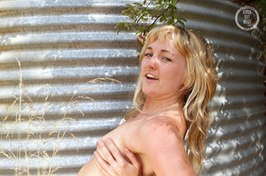 Foxy blonde teases with her steaming hot body outdoor before she peels off her red blouse and bares her juicy boobs then pulls down her red panty and expose her sweet pussy in different poses by a watertank. - XXXonXXX - Pic 9