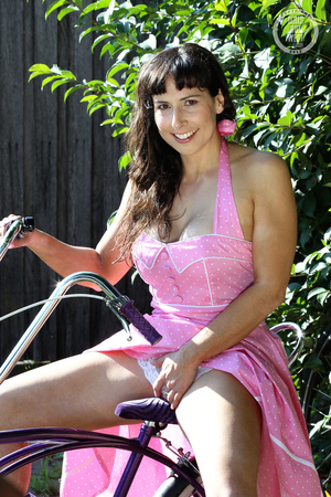 Luscious babe pose her foxy body then reveals shows her lusty pussy wearing her pink dress and white panty in a garden before she gets naked and shows her sweet boobs while she nails her sweet crack on a purple bike. - XXXonXXX - Pic 2