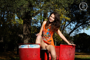 Smoking hot brunette shows her sweet tits and juicy pussy as she pose her smoking hot body in different positions in a playground wearing her orange dress and black and white sneakers. - XXXonXXX - Pic 1
