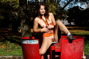 Smoking hot brunette shows her sweet tits and juicy pussy as she pose her smoking hot body in different positions in a playground wearing her orange dress and black and white sneakers. - XXXonXXX - Pic 5