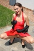 Sexy brunette in black leather gloves and red dress seductively posing