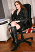 Brunete in glasses and leather outfit posing by the white table and gets