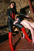 Smoking lass in leather bodysuit and red boots forced masked guy to suck