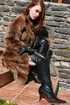 Young redhead in leather boots and fur coat teasing outdoors and flashing