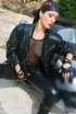 Tall biker girl in leather uniform and bandanna strips outdoors by the