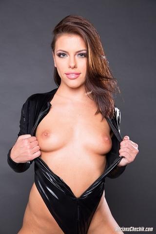 leather-clad brunette slowly revealing