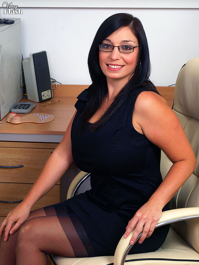 Hot brunette mom with huge boobs undresses to pose in retro stockings in the office