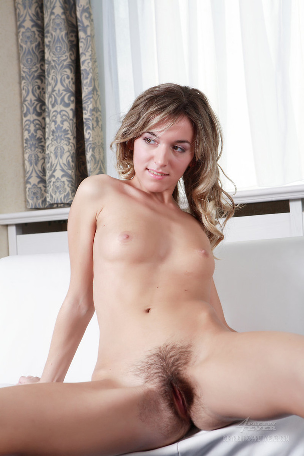 Nude broad shows off her hairy pussy on a white couch.