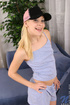 Cute teen with a pink westcoast trucker hat lifts up her shirt to show