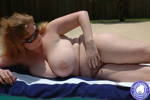 Big breasted redhead sunbathing by the p - XXX Dessert - Picture 1