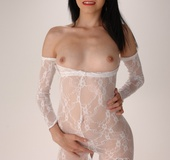 Hot brunette wearing a white lace cat-suit torn hole revealing her snatch