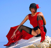 Nasty mom in sexy stockings, hat, red top and umbrella posing on the rocks