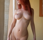 Bodacious red-haired chick with awesome boobs enjoys posing naked on cam