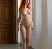 Magnificent red girl with sexy body posing naked demonstrating her grace
