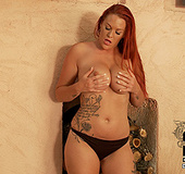 Tattooed red bitch licking her huge boobs with pierced nipple in dirty