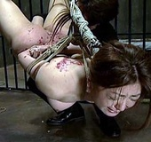 Hogtied and hung Asian girl tortured with hot wax