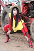 Black haired babe in red latex posing with a tractor
