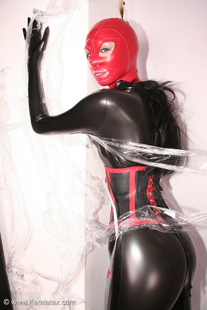 Sexy brunette in black latex jumpsuit ta - XXX Dessert - Picture 14