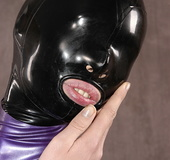 Masked girl in black and lilac latex jumpsuit posing and shows her pretty