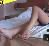 Hot blonde temptress on the bed teases with her long shapely legs, wide