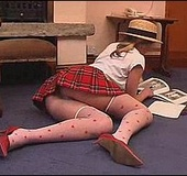 Naughty blonde school girl in uniform playing with a lollipop