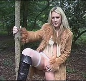 Blonde whore in stockings, high boots and a fur coat masturbating in the